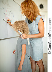 Little girl with mom writing on board with marker. Learning and school concept.
