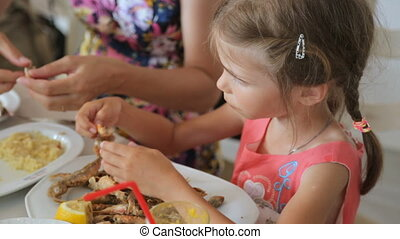 Little girl with mother eating at cafe