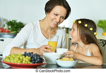 Little girl with mother eating