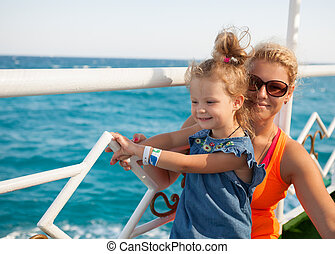 little girl with mother looking at sea