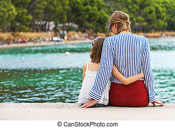 Little girl with mother sitting on the pier.