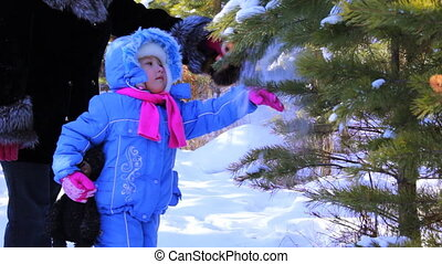 Little girl with mother walking outdoor in the winter pine forest
