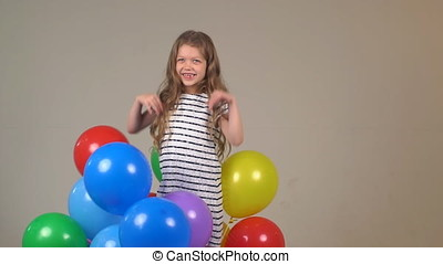 Little girl with multi-colored balloons. The child joyfully raises her hands up and smiles. slow motion