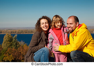 Little girl with mum and daddy, in bright autumn day. Happy family on nature.
