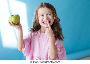 little girl with no teeth eats fruit apple