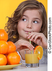 Little girl with oranges and a glass of juice