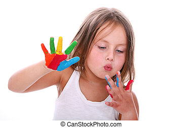 little girl with painted hands blowing on it