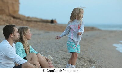 Little girl with parents relax near the sea