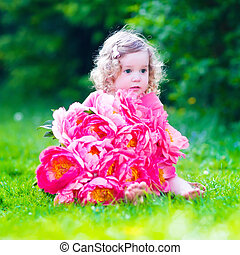Little girl with peony flowers in the garden - Little cute...