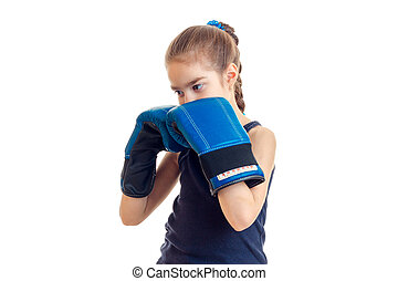 little girl with pigtail stands in the large blue boxing gloves in front of a camera