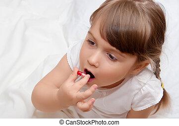 Little girl with pill