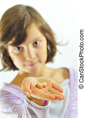 little girl  with pills in hand
