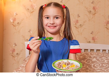 Little girl with plate and spoon in hands.