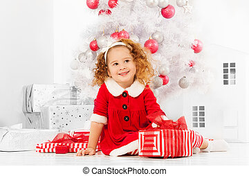 Little girl with presents under the Christmas tree