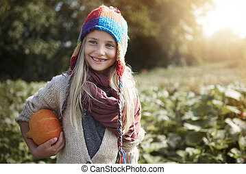 Little girl with pumpkin in the field