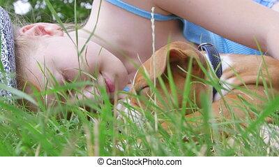 Little girl with puppy dog sleeping in summer garden