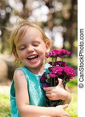 little girl with purple flowers bouquet on green grass