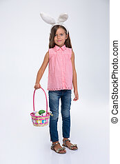 Little girl with rabbit ears holding basket of eggs