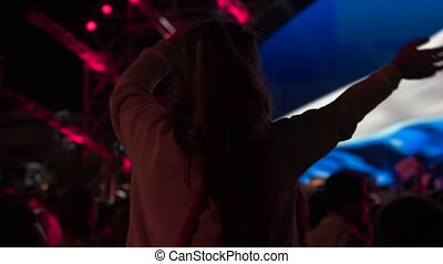 Little girl with raised hands in a crowd of fans at a music concert