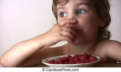 little girl with raspberry