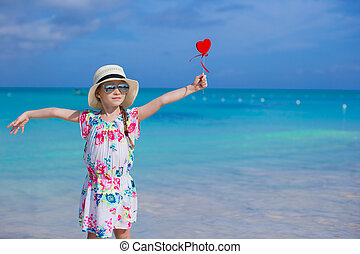 Little girl with red heart in hands on a tropical beach