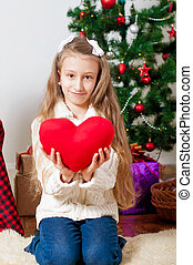 little girl with red heart toy