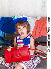 Little girl with red mother bag and new clothes. Child choosing her clothes. View a lot of wardrobe. Wow.