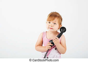 little girl with retro phone against a white
