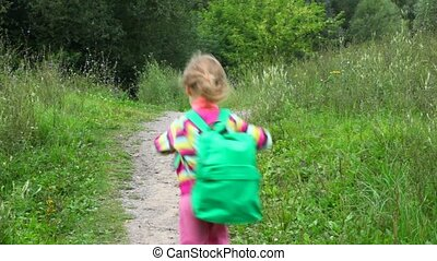 little girl with rucksack running in park from camera