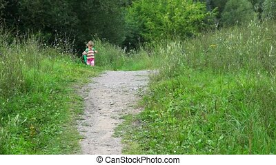 little girl with rucksack running in park to camera