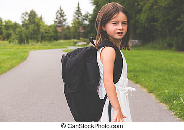 Little girl with school backpack on path looking back to camera