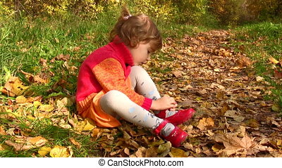 little girl with shoes in autumn park