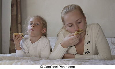 Little girl with sister eating pizza lying in front of TV