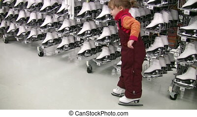 little girl with skates in shop