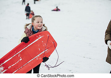 Little Girl with Sled in the Snow