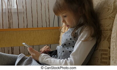 Little girl with smartphone on couch