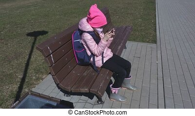 Little girl with smartphone on the bench