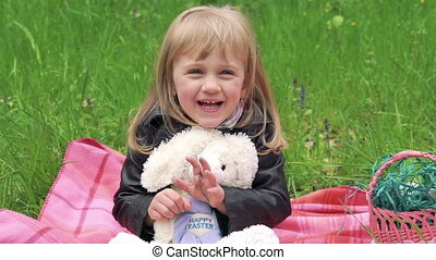 Little girl with soft toy smiling on a camera. Slowly