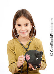 little girl with stethoscope and piggy bank