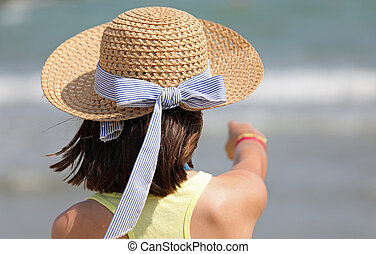 little girl with straw hat in summer