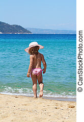 little girl with straw hat on beach