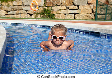 Little girl with sun glasses having fun in the pool