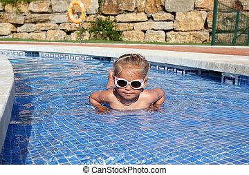 Little girl with sun glasses having fun in the pool