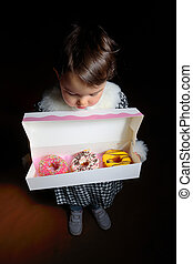Little girl with sweet different donuts