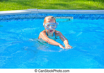 little girl with swim goggles - Little blond girl wearing...