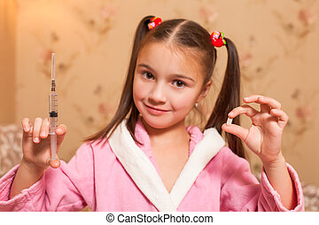 Little girl with syringe and tablet in her hands