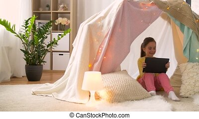 little girl with tablet pc in kids tent at home - childhood,...