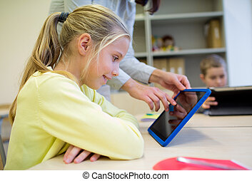 little girl with teacher and tablet pc at school