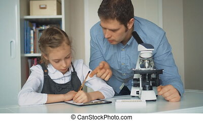 Little girl with teacher in science class with microscope on the table.