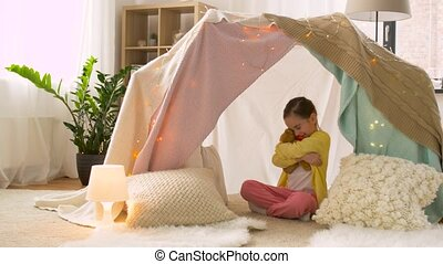 little girl with teddy bear in kids tent at home